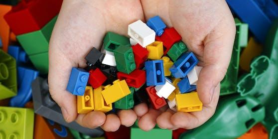 Spielsteine eines bekannten Herstellers in den Händen von Kindern. (Symbolbild)