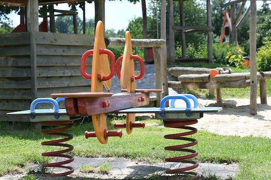 Spielgeräte für Kinder mit Schaukel und Rutsche auf einem Spielplatz
