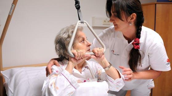 Eine Patientin betreut von einer Diplomkrankenschwester hält sich an einer Triangel-Aufrichtungshilfe fest. Symbolbild