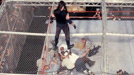 Der Undertaker versenkt Mankind durch den Käfig