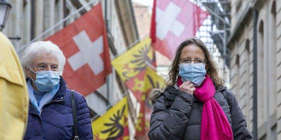 Menschen mit Schutzmasken auf einer Straße in Genf, Schweiz