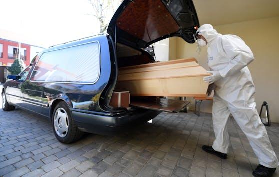 Ein Bestatter in Schutzkleidung schiebt einen Sarg in einen Leichenwagen. Symbolbild