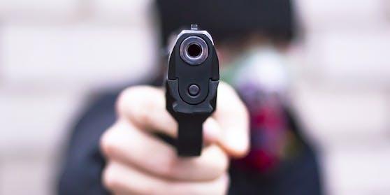 Ein Mann bedroht sein Gegenüber mit einer Pistole. Symbolbild