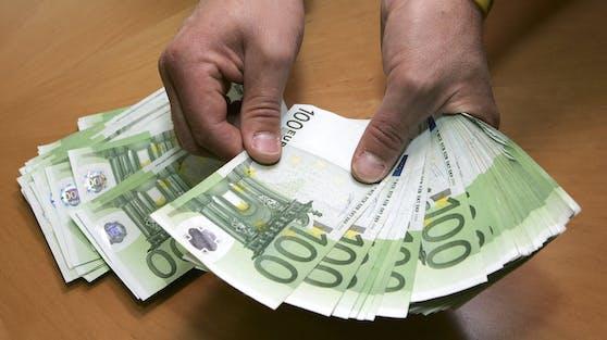 Ein Mann zählt Euro-Banknoten. (Symbolbild)