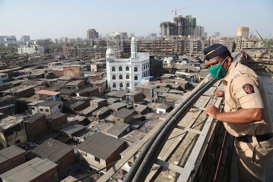 Ein indischer Polizist blickt auf das Slum-Viertel Dharavi in Mumbai, Maharashtra. Symbolbild