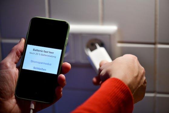 Ein Smartphone-Ladegerät wird in eine Steckdose gesteckt. Symbolbild
