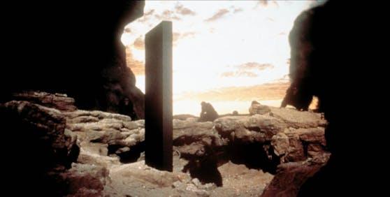 """Szene aus """"2001: A Space Odyssey"""": Steinzeitliche Affenmenschen untersuchen einen seltsamen Monolithen in der Wüste"""