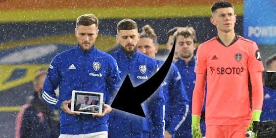 Leeds-Kapitän Cooper (l.) hält das Tablet in der Hand.