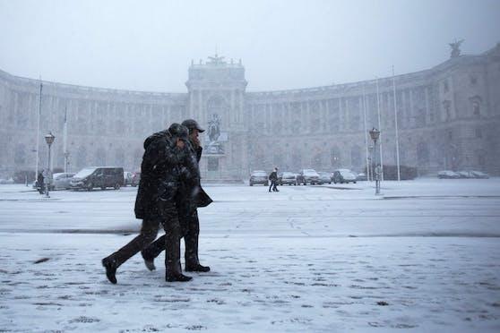 Passanten spazieren bei Schneefall über den Wiener Heldenplatz