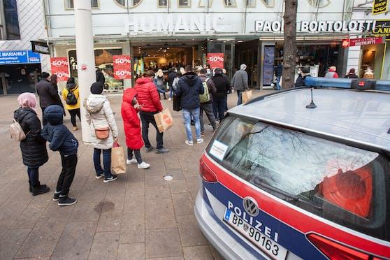 Polizeifahrzeug stehen vor der überfüllten Filiale einer Schuhmodenkette in der Mariahilfer Straße in Wien am 4. November 2020