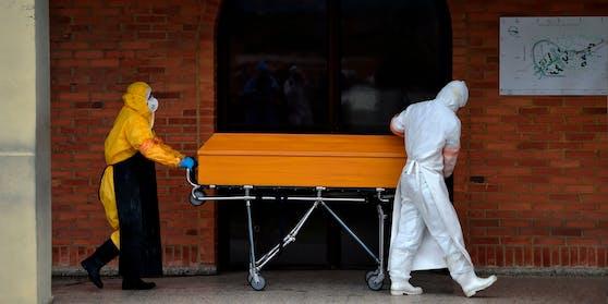 Arbeiter in Schutzkleidung transportieren einen Corona-Toten in einem Sarg. (Symbolbild)