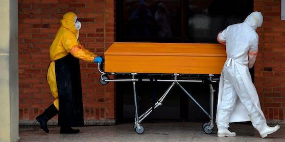 Arbeiter in Schutzkleidung transportieren einen Corona-Toten in einem Sarg. Symbolbild