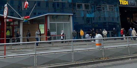 Menschenansammlung vor einer Bank in Simmering