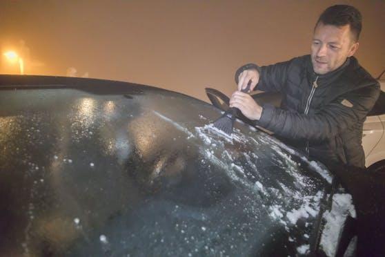 Ein Mann kratzt Eis von der Windschutzscheibe eines Autos. Symbolfoto