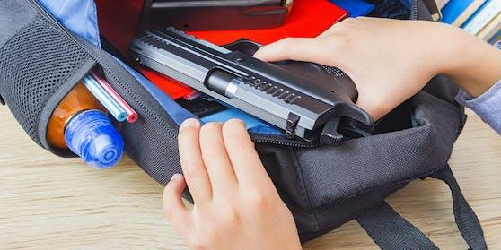 Ein junger Schüler zieht eine Pistole aus seinem Rucksack. (Symbolbild)