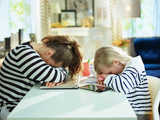 Müde Eltern und Kinder beim Homeschooling im dritten Lockdown