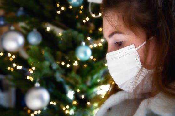 Porträt einer jungen Frau mit schützender Gesichtsmaske vor einem Christbaum: So sieht unser Weihnachten aus.