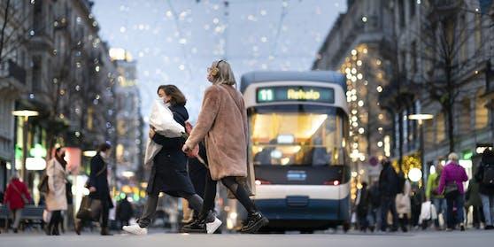 Personen mit Schutzmasken und Einkauftaschen gehen auf der Bahnhofstraße in Zürich.