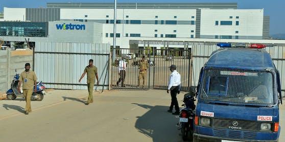 Polizisten bewachen den Eingang zum Werksgelände der Wistron Corp. nach den schweren Ausschreitungen von Samstagfrüh.