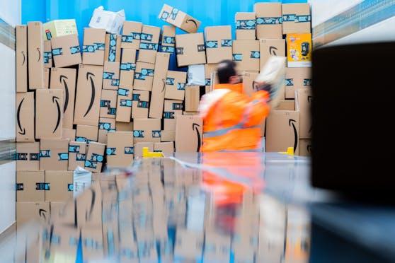 Ein Mitarbeiter verlädt Amazon-Packerl in einem Lkw. Amazon gab mögliche Lieferverzögerungen bekannt.