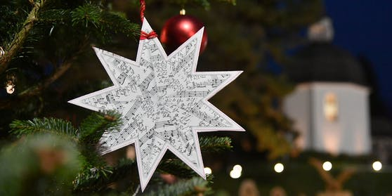 Ein Weihnachtsstern mit den Noten vor der Stille Nacht-Kapelle in Oberndorf