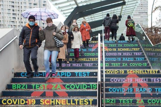 Menschen tragen Schutzmasken und Regenschirm am Weg zu dem Antigen Schnelltest an einer Stiege bei dem Austria Center Vienna in Wien.
