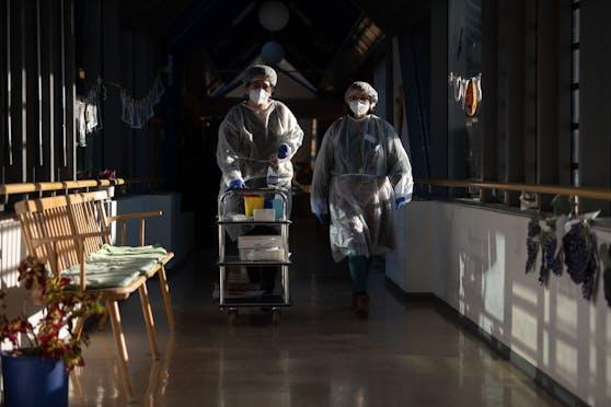 Zwei Altenpfleger in Schutzmontur im Einsatz. Symbolbild