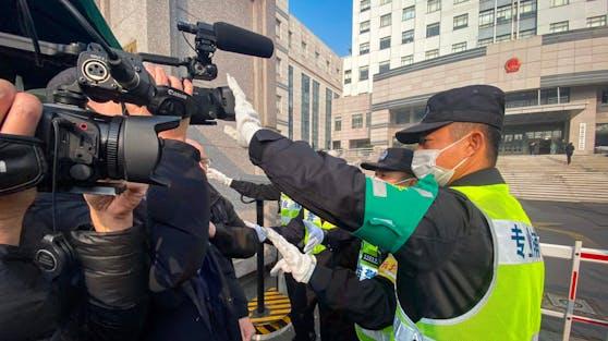 Ein Polizist deckt eine Kamera ab, um Journalisten an der Aufnahme von Filmmaterial vor dem Gericht zu hindern, wo Zhang Zhan vor Gericht steht.