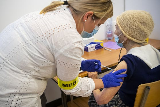 Eine Krankenschwester gibt einem älteren Patienten in Neuenburg die erste Dosis des Pfizer-BioNTech-Impfstoffs.