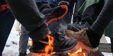 Flüchtlinge wärmen sich an Feuer – Österreich hilft