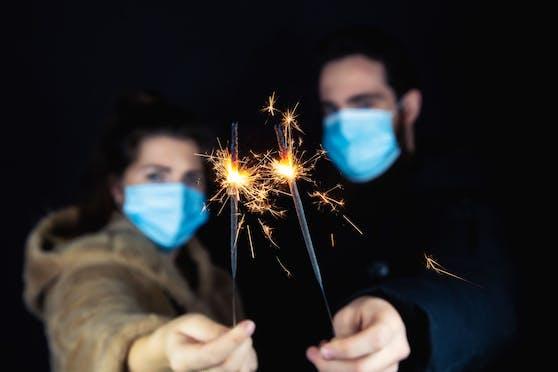 Sieht so Silvester 2020 aus? Ein junges Paar mit Gesichtsmasken und Wunderkerzen