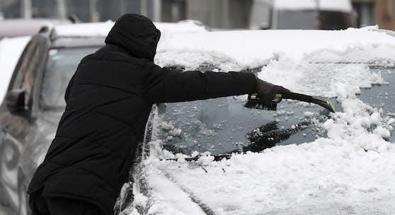 Ein Mann befreit am 3. Dezember 2020 sein Fahrzeug vom gefallenen Schnee in Wien.