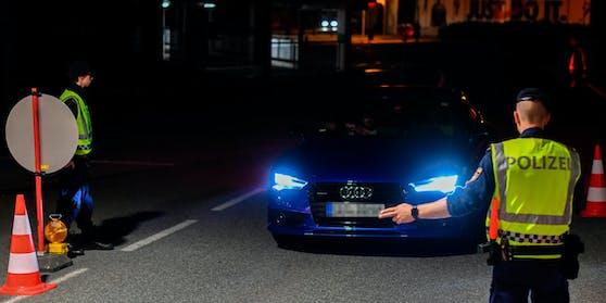 Polizisten kontrollieren einen Pkw-Lenker. Symbolbild.