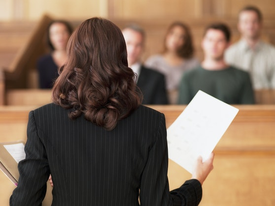 Symbolfoto einer Frau mit Dokumenten vor Gericht.