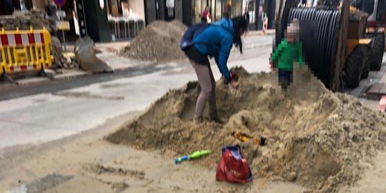 Eine Frau und ihr Kind nutzen die Baustelle in der Neubaugasse als Spielplatz