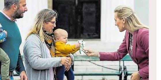 Ministerin Aschbacher inszeniert sich dabei, einem Baby einen 100-Euro-Schein zu überreichen.