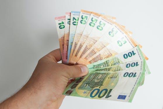 Ein Mann hält Euro-Geldscheine in der Hand. Symbolbild