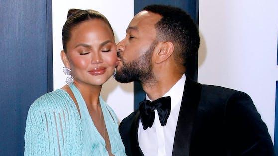 John Legend(re.) und seine Frau Chrissy Teigen werden zum dritten Mal Eltern. Die Babynews haben sie in Legends neuem Musikvideo verraten.