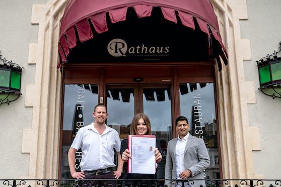 Bei ihrer neuen Lehrstelle: Samantha T. mit Rathaus-Café-Besitzer Martina Schödl und Gewerkschafter Sumit Kumar