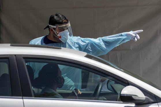 Ein Mitarbeiter einer Drive-In Corona-Teststation in Lake View Terrace, Kalifornien, erteilt am 30. Juni 2020 einer Autofahrerin Anweisungen