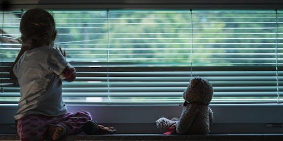 Ein kleines Mädchen schaut traurig aus dem Fenster. Symbolbild