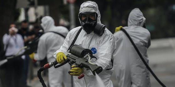 Medizinisches Personaldesinfiziert den Congonhas Flughafen in Sao Paulo.An nur einem Tag haben sich in Brasilien 45.000 Menschen mit dem Virus infiziert.