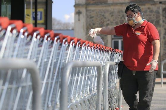 Ein Billa-Mitarbeiter in Schutzmaske desinfiziert Einkaufswägen.