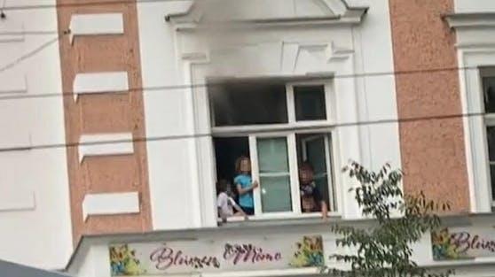 Die Kinder standen wegen des starken Rauches am Fenster.