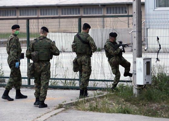 Kroatische Grenzpolizisten patrouillieren um ein Flüchtlingscamp.