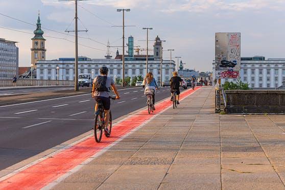 Die ersten Radfahrer fahren schon am roten Radweg.