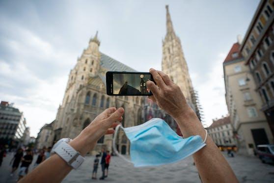 Eine Frau mit Mund-Nasen-Schutz Maske fotografiert am Sonntag, 26. Juli 2020, den Stephansdom in Wien