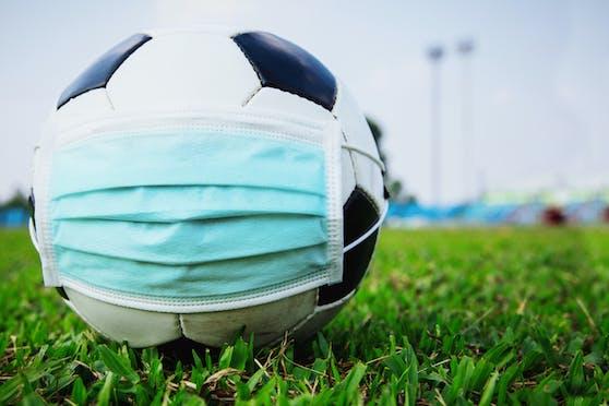 Symbolfoto eines Fußballs mit Corona-Maske.