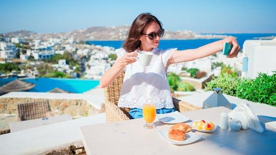 Eine junge Frau macht ein Selfie beim Frühstück in einem griechischen Lokal. Symbolbild