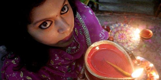 """Eine junge Frau hält eine Öllampe während des """"Lichterfestes"""" in Kalkutta. Archivbild"""